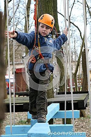 Child climbing in adventure playground.