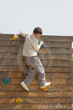 Child climbing a wooden wall