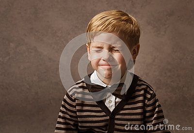 Child with closed eyes. Boy in brown retro bow tie