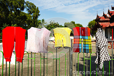 Child clothes and rags drying on a fence