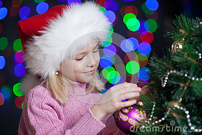 Child decorating Christmas tree on bright backdrop