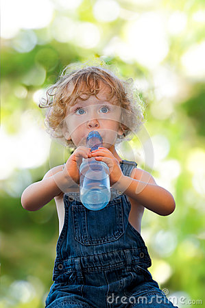 Child in denim suit drinking water
