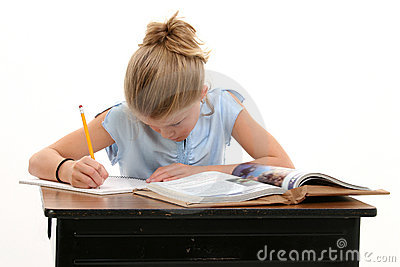 Child Doing School Work At Desk