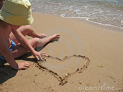 Child draw heart on beach