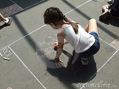 Child drawing on the asphalt chalk
