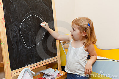 Child drawing with chalk on blackboard