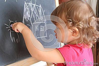 Child draws on the blackboard