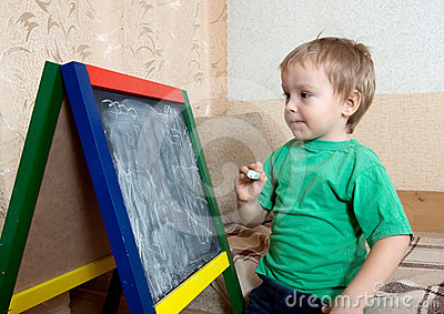 Child draws on  blackboard with chalk