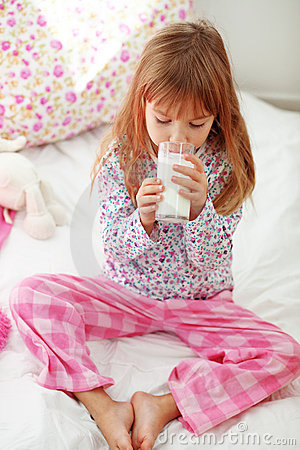 Child drinking milk in bed