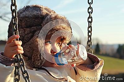 Child drinking water from feeder