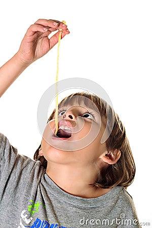 Child eating pasta noodle