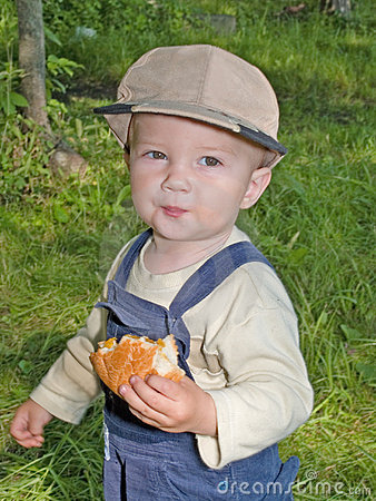Child eating the roll in the park outdoor