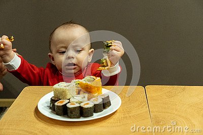 Child eating sushi at home, cute baby Stock Photo