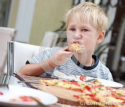 Child eats pizza.