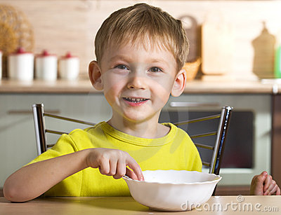 Child eats from a white bowl
