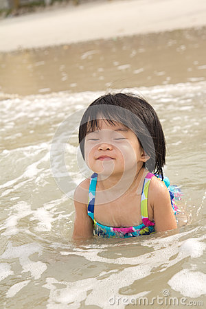 Child enjoy waves on beach
