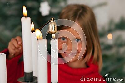 Child extinguishing Christmas candles