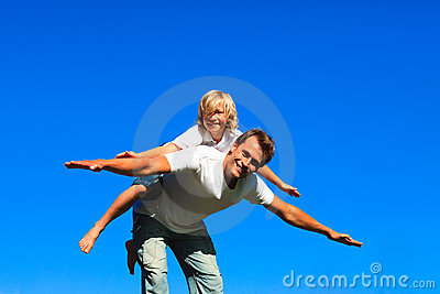 Child on father s back playing airplane