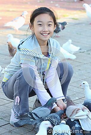 Child feeding pigeon