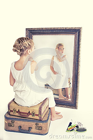 Free Child Fixing Her Hair While Looking In The Mirror. Stock Images - 58101244