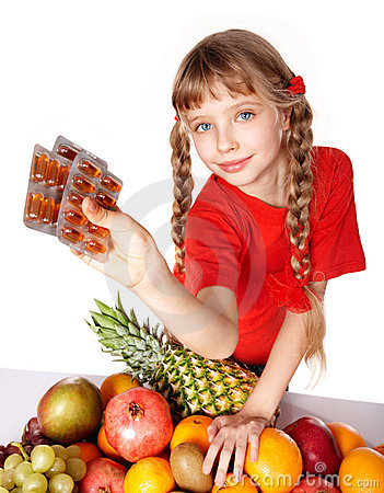Child with fruit and vitamin pill.