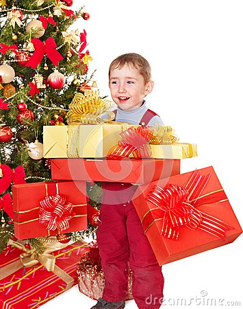 Child with gift box near Christmas tree.