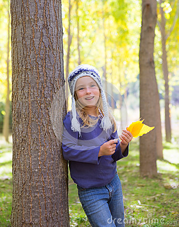 Child girl in autumn poplar forest yellow fall leaves in hand