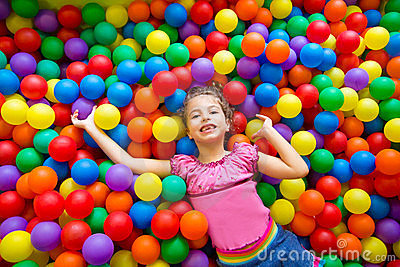Child girl on colorful balls playground high view