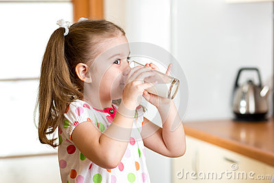 Child girl drinking yogurt or milk in kitchen