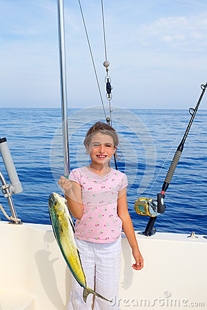 Child girl fishing in boat with mahi mahi dorado fish catch