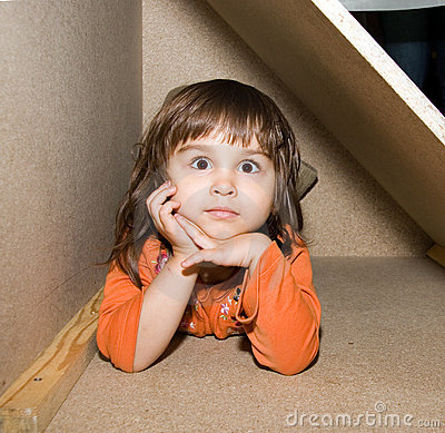 Child girl hiding in wooden box, dreams alone
