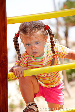 Child girl on ladder in playground.