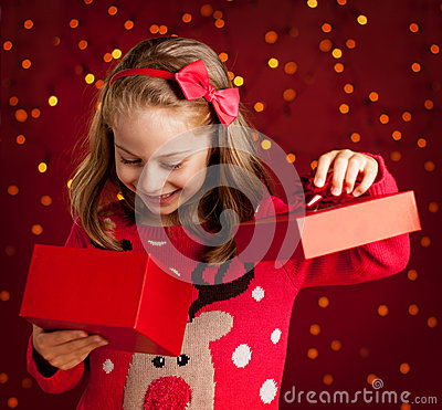 Free Child Girl Opens Christmas Present On Dark Red With Lights Royalty Free Stock Image - 44141156