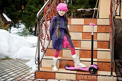 Child girl posing with scooter on house steps
