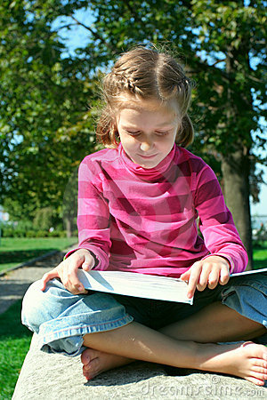 Child girl reading at the park