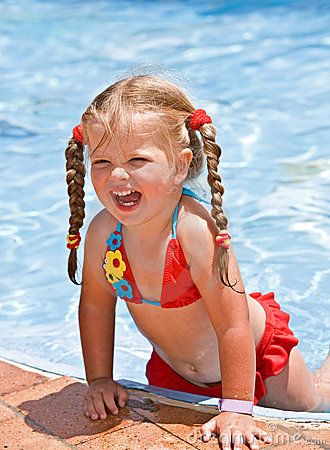 Child girl in red bikini near blue swimming pool.