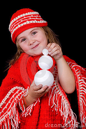 A child girl wearing winter clothes is holding a l