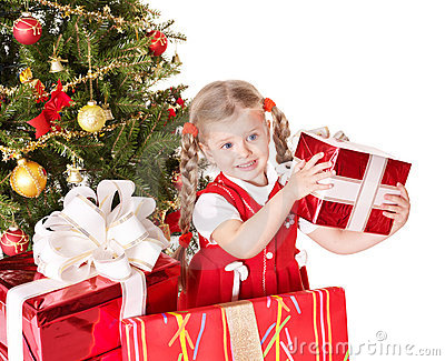 Child giving gift box by christmas tree.