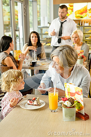 Child with grandmother at cafe eating cake