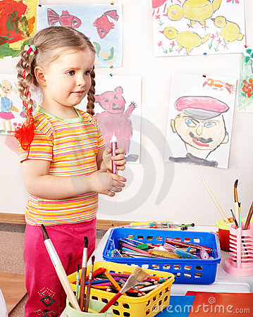Child with group of colour pencil in play room.