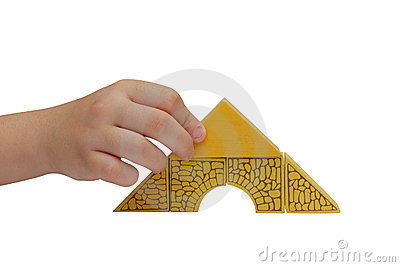 Child hand make a building with yelloow blocks