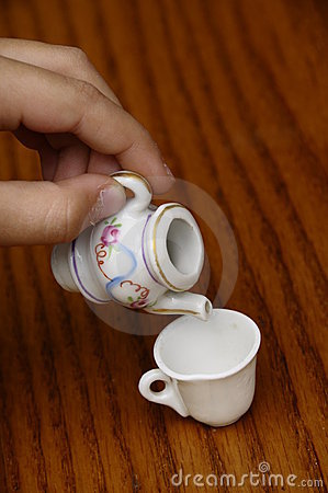 Child hand pretending to pour tea