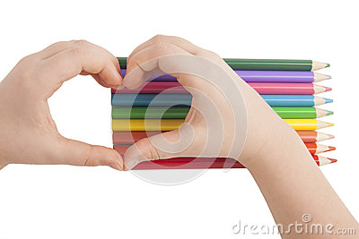 Child hands form a heart shape above color pencils