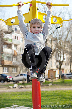 Child hanging on a horizontal bar