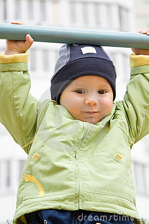 The child hanging on a horizontal bar