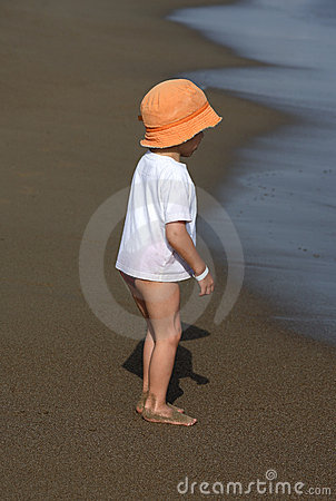 Child in hat standing on the beach