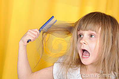 Child having problem with brushing her hair