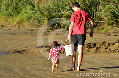 Child helps to carry a heavy bucket