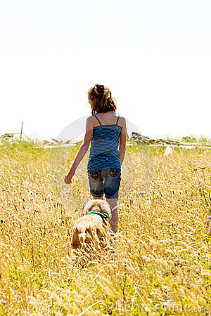 Child and her puppy walking in a field of grass