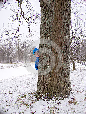 Child hidden behind a tree